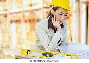 female architect - mid adult architect examining blueprints...