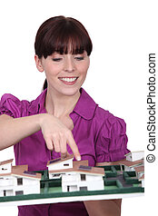 Female architect presenting her model.