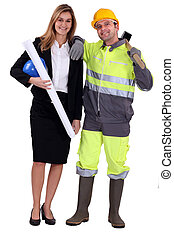 Female architect stood with manual worker