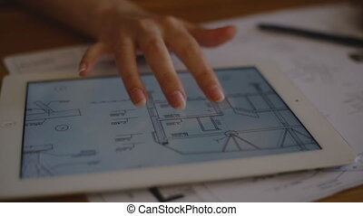 Female Architect Studying Plans In Office at desk with plans...