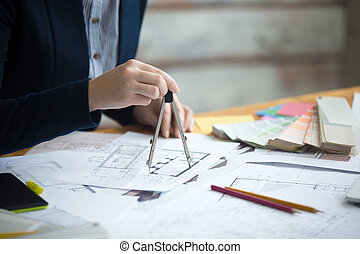 Female architect using drawing compass
