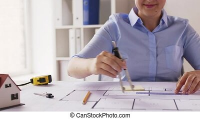 female architect with compass measuring blueprint