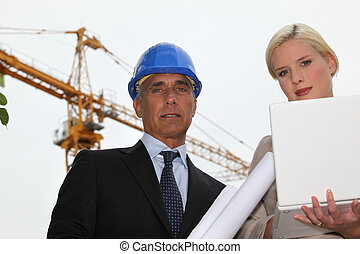 female architect with foreman in construction site