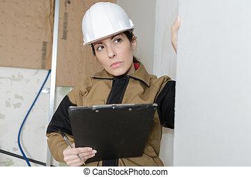 female architect with hardhat taking notes