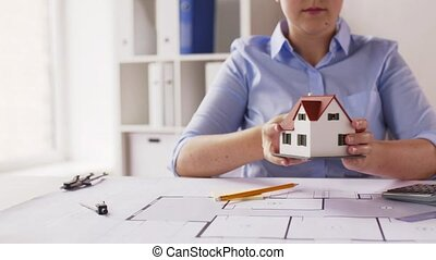 female architect with house model and blueprint -...