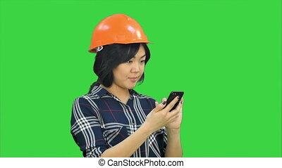 Female architect with orange helmet using smartphone on a Green Screen, Chroma Key