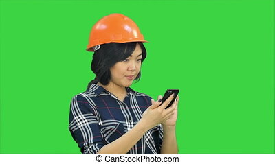 Female architect with orange helmet using smartphone on a Green Screen, Chroma Key