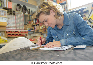 female architect working on blueprint at table in workshop