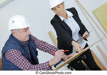 female architect working with construction worker at site