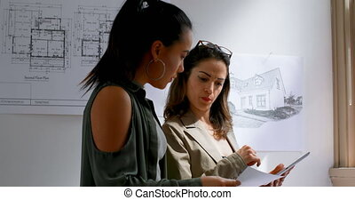 Female architects discussing a blueprint plan 4k - Female...