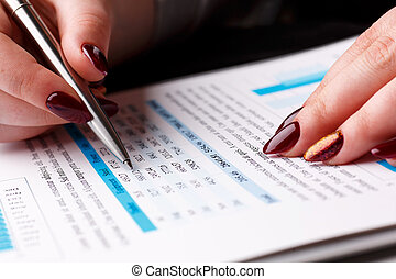 Female arm hold and point silver pen in financial graph...