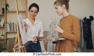 Female art teacher is explaining new information to student at painting lesson in studio pointing at picture and talking, girls are laughing having good time.