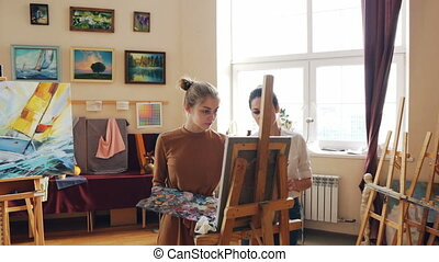 Female art teacher is working with good-looking young girl...