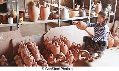 Woman chooses pots clay pots in store warehouse