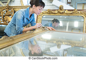 female artisan working on a big wooden picture frame