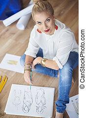 Female artist drawing fashion sketches