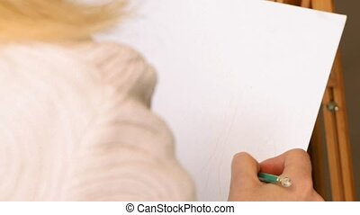 Female artist draws a pencil sketch in art studio