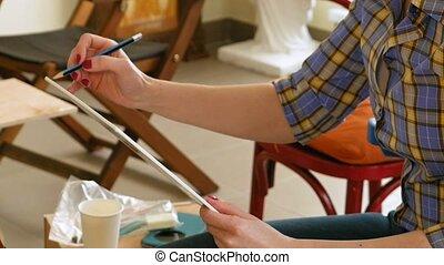 Female artist draws a pencil sketch in art studio