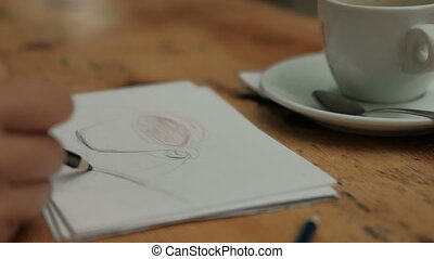 Female artist draws picture sitting at table in cafe indoors.