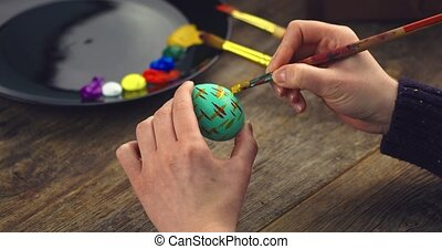 Female artist hands painting on Easter egg preparing for christian religious holiday, close up video. High quality 4k footage