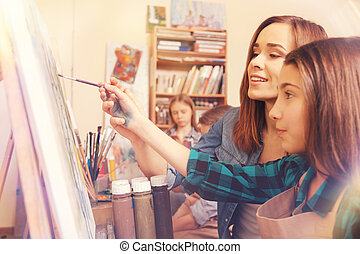 Female artist helping young student with abstract painting -...