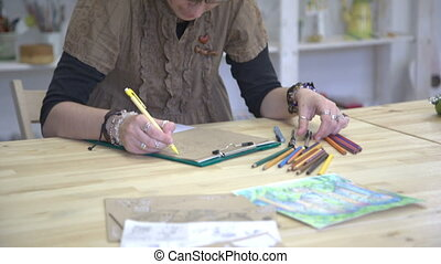 Female artist is drawing picture or sketch on brown paper.