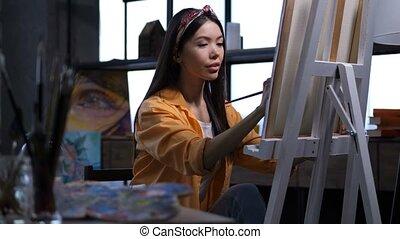 Female artist making a painting at art studio