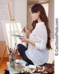 female artist near easel with blank canvas - female artist ...