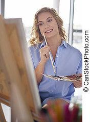Female artist painting artwork on canvas
