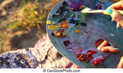 Female artist painting outdoor closeup palette knife -...