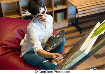 Female artist painting with palette and paintbrush on canvas
