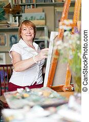 Female artist paints a picture on canvas