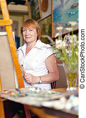 Female artist paints a picture