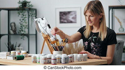 Beautiful female artist sitting at workplace and preparing brushes with paints for drawing. Young blonde painting on canvas in studio. Art concept.