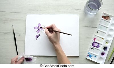 Female artist starting a creative watercolour painting of a purple flower viewed from overhead with a close up on her hand