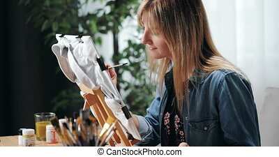 Side view of attractive female artist sitting at own studio and painting on grey t-shirt. Positive woman using color palette and brush for drawing at workplace.