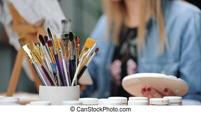 Close up of female artist using color palette for drawing on clothing in studio. Young woman sitting at table with various brush and refreshing old t-shirt.