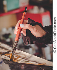 Female artists hand holding big brush. Woman painting picture.