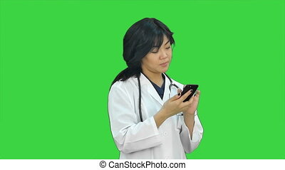 Female asian doctor wearing a white coat and stethoscope looking at x ray on a Green Screen, Chroma Key