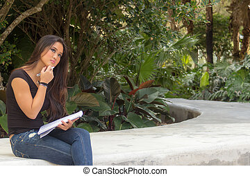 Female asian student sitting outside thinks while writing in notebook journal