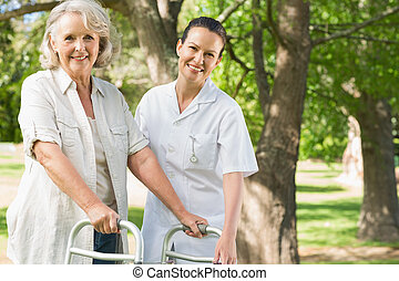 Female assisting mature woman with walker at park