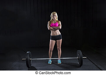Female Athlete - A female college student lifts weights
