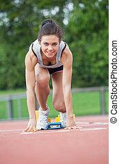 Female athlete at starting blocks
