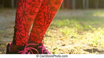 Female athlete doing exercise in forest 4k - Low section of...