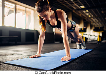 Female athlete doing push-up exercises in gym - Female...
