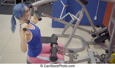 Female athlete doing wide grip pulldowns exercise in gym....