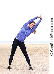 Female athlete doing yoga in sand