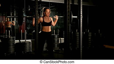 Female athlete exercising with barbell 4k - Front view of ...