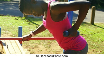 Female athlete exercising with dumbbell in the park 4k -...