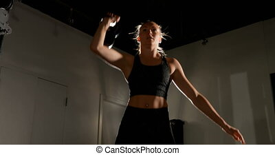 Female athlete exercising with kettlebell 4k - Front view of...